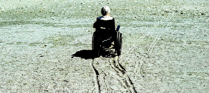 Woman on the beach with wheel chair
