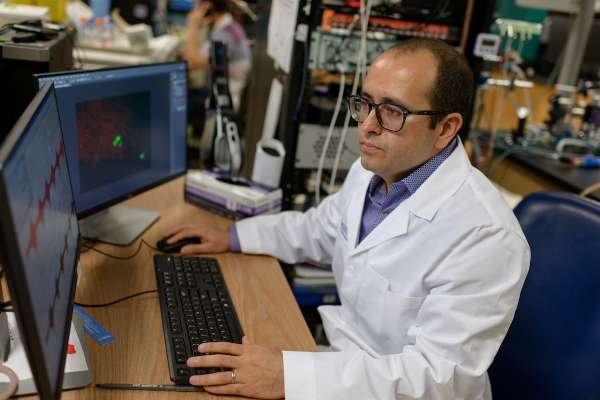 Dr. Arash Tadjalli working on a computer