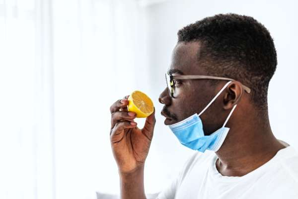 black man sniffing a lemon with a mask under his chin