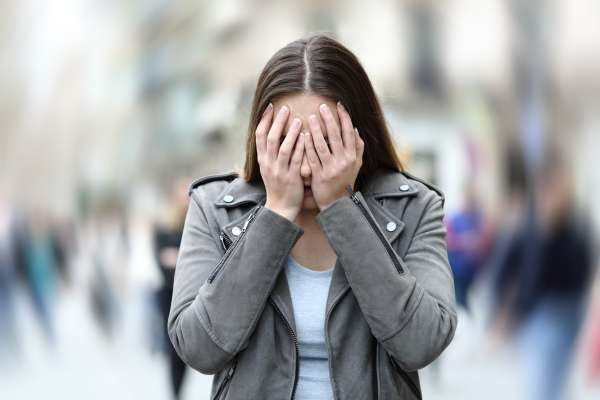 Front view of a woman suffering social anxiety attack on city street