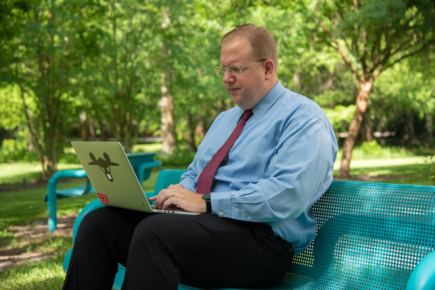 Kevin Hanson sitting on a bench and working on his computer outside
