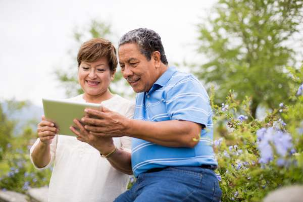 Smiling senior couple using digital tablet in a park
