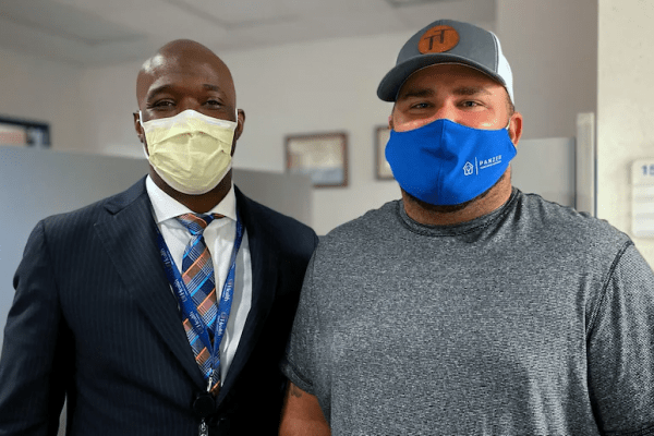two men smile through their masks. One of the men has his sleeve rolled up, indicating his vaccination.
