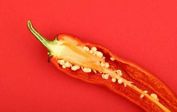 a red pepper is cut in half against a red background