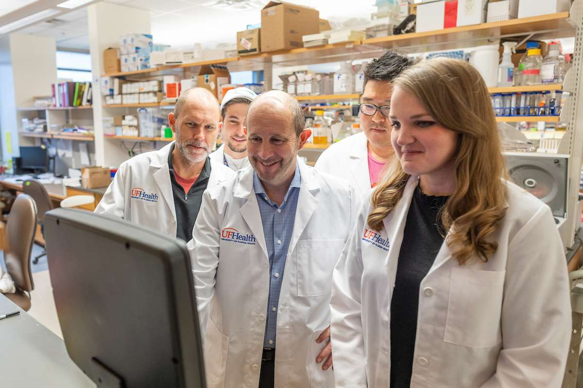 Drs. Todd Golde and Cara Croft collaborate with trainees in the lab.