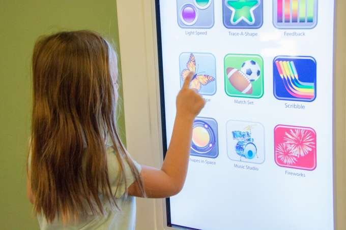 Child playing a computer game on a giant touchscreen