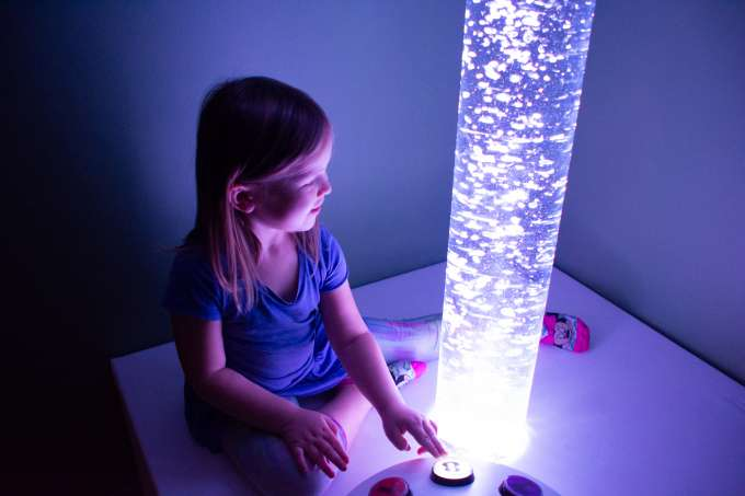 Child in low stimulation playing with a colorful tube that lights up different colors with assorted buttons.