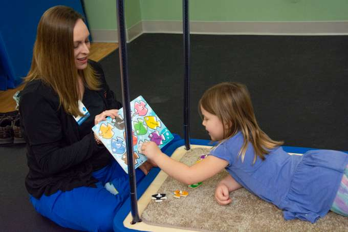 Nurse plays a game with child to fit the blocks while child lays belly down on a swinging surface to practice movements