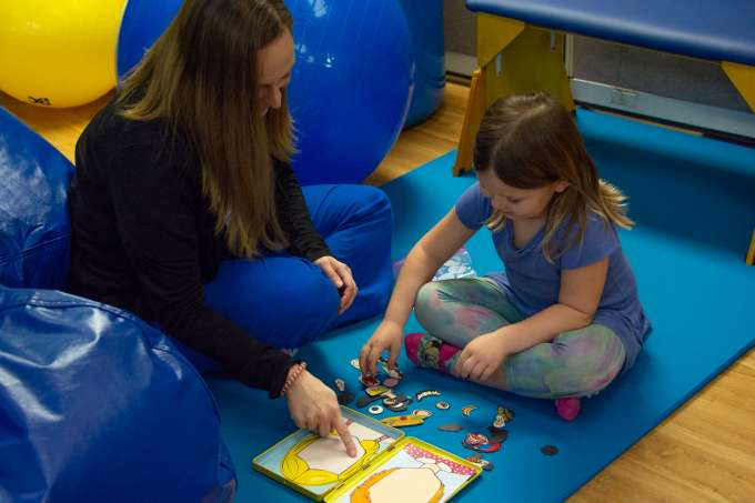 Nurse playing with child to demonstrate parts of a human face