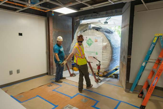 Men placing the MRI in the correct room