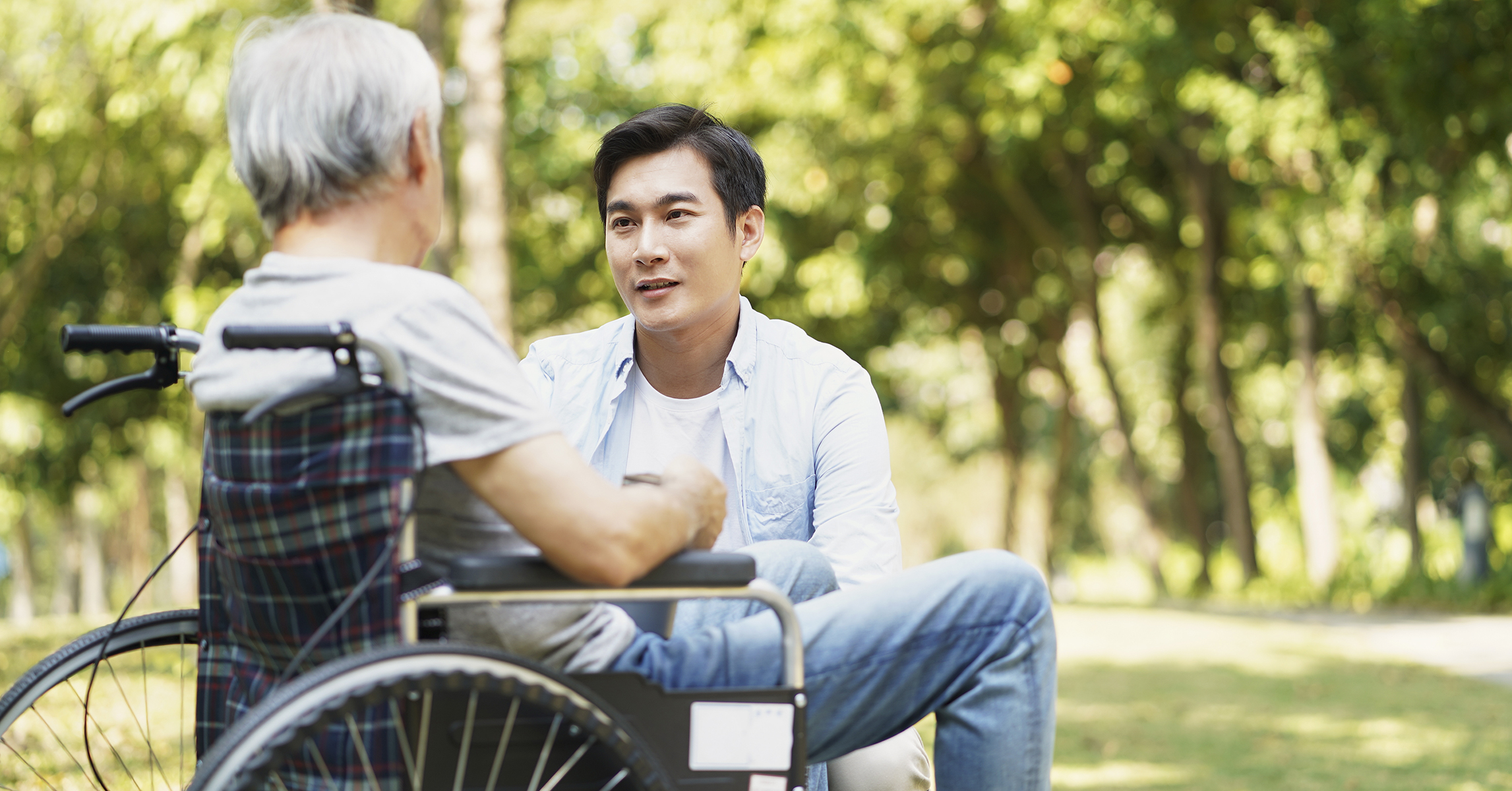 asian adult child talking to senior father outdoors
