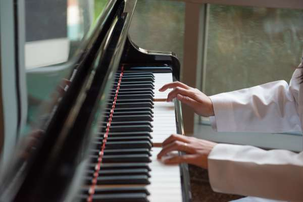close up of Aprinda's hands playing piano