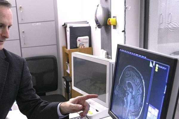 doctor vaillancourt inspecting a scan by an m-r-i